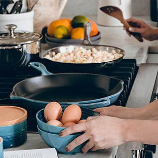 Image of a person's hands grasping a bowl of eggs beside a cast iron pan warming on the stovetop.
