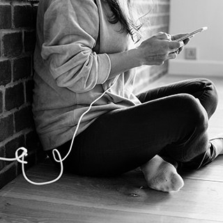 Black and white image of a person from the shoulders down typing on a cellphone that is plugged into the wall