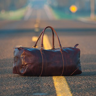 Leather duffle bag sits in the middle of a road with a blurred background