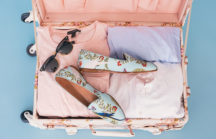 Pink suitcase with sunglasses, floral shoes, and pastel-colored clothing inside.