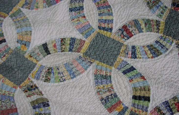 Hand pieced and quilted quilt on white background