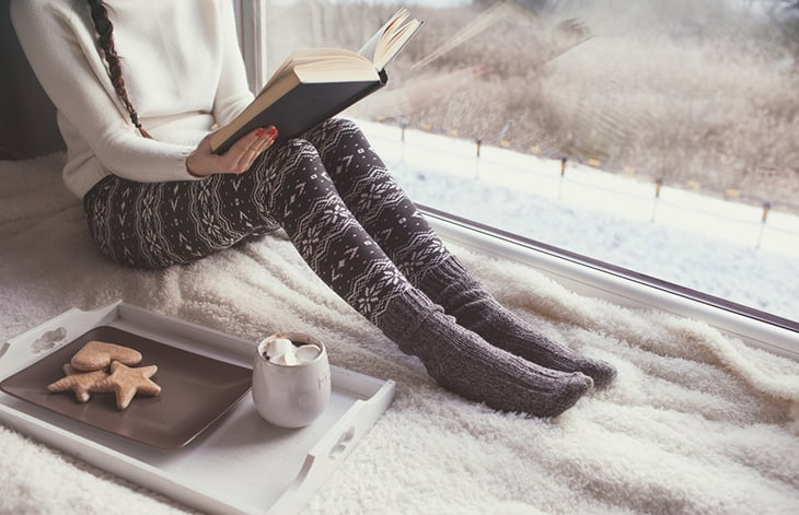 a person in black and white winter leggings and gray socks sits on a blanket reading a book beside a tray of cookies