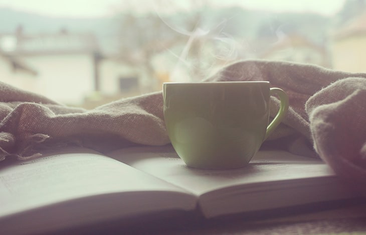 a steaming mug sitting on top of an open book with a warm shawl beside it