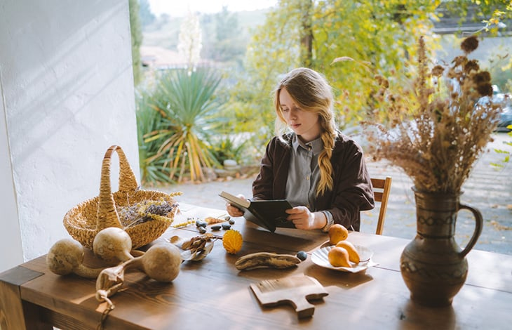 A person with braided hair sits at a wooden table surrounded by wabi-sabi objects