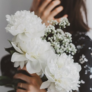 Person holding white flowers and babies breath