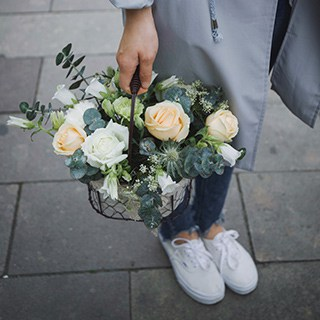 Person holding a basket of cut flowers