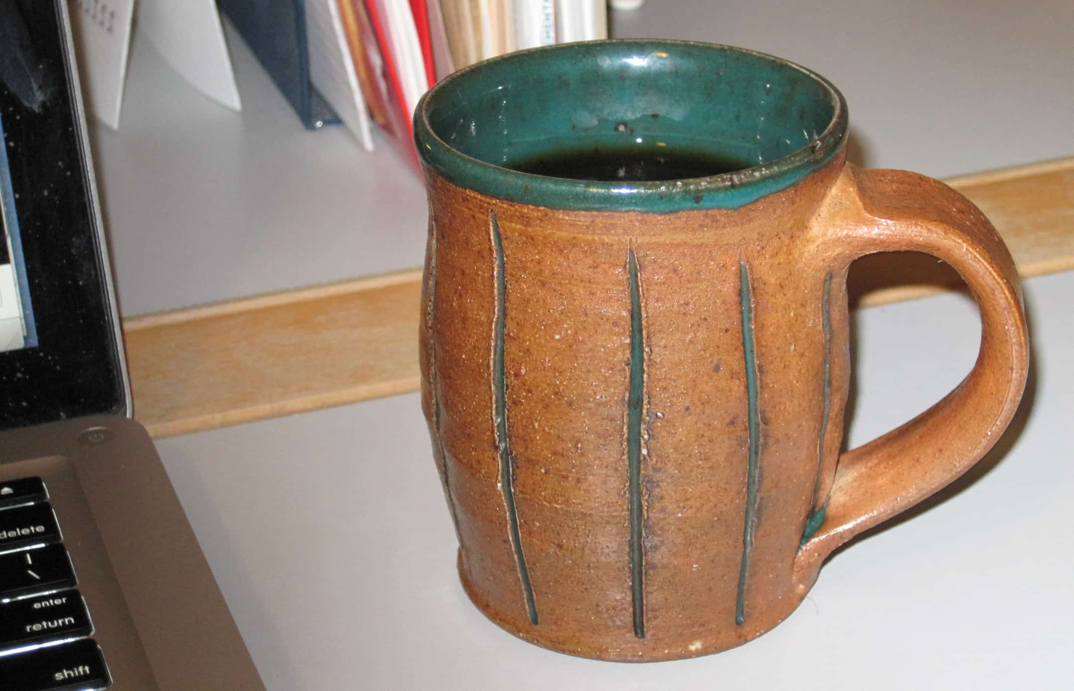green and brown handmade ceramic mug—mindful consumption
