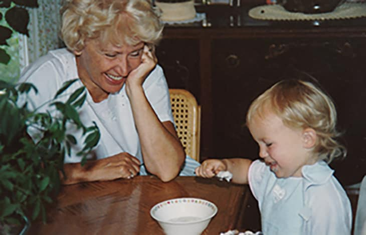 Toddler eating with a spoon at a wooden table with their grandmother