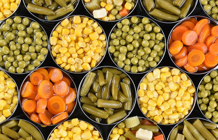 peas, corn, green beans, and carrots stored in open cans