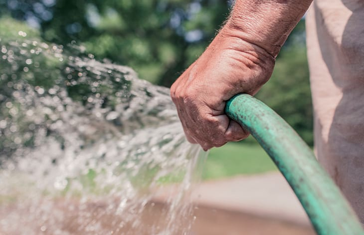 close-up of a fist holding and spraying a green garden hose