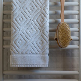 white towel with geometric imprinting hanging next to a shower brush