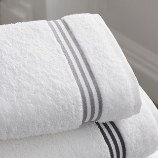 two folded white towels with gray-striped trim on a gray background