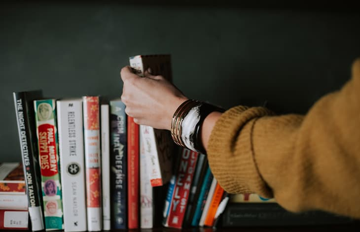an arm with a tan-gold sweater and bracelets pulling a book off a bookshelf