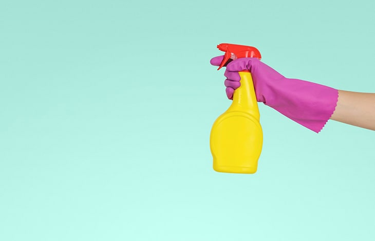 pink-gloved hand holds yellow and red spray bottle of disinfecting solution on a mint-colored background
