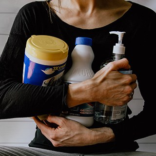 a person in a long-sleeve black shirt wraps their arms around containers of disinfecting wipes, bleach, and hand sanitizer