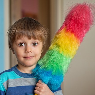 a child holds a rainbow colored duster