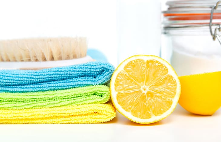 cut lemon and mason jar of cleaning liquid sits beside a cleaning brush on top of a stack of brightly colored rags