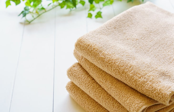 folded tan towels on white backdrop