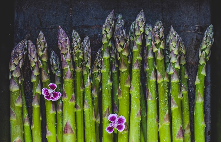 asparagus tops on a dark background with flowers