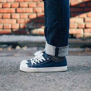 A person's legs and feet stand wearing jeans and navy-blue trainers with bright, clean white laces  on concrete in front of a brick wall