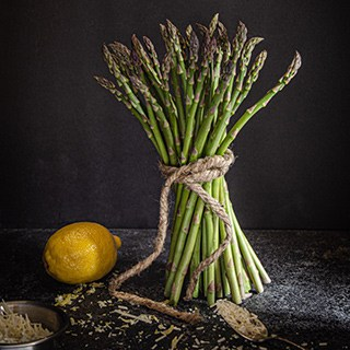 standing bouquet of asparagus tied with twine next to a whole lemon