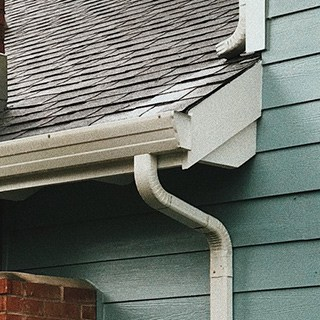 corner of roof and clean gutter on a seafoam-green house