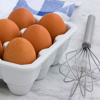 eggs stored in ceramic white container next to a kitchen whisk