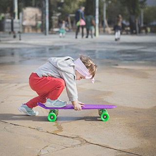 a child riding a purple skateboard with green wheels