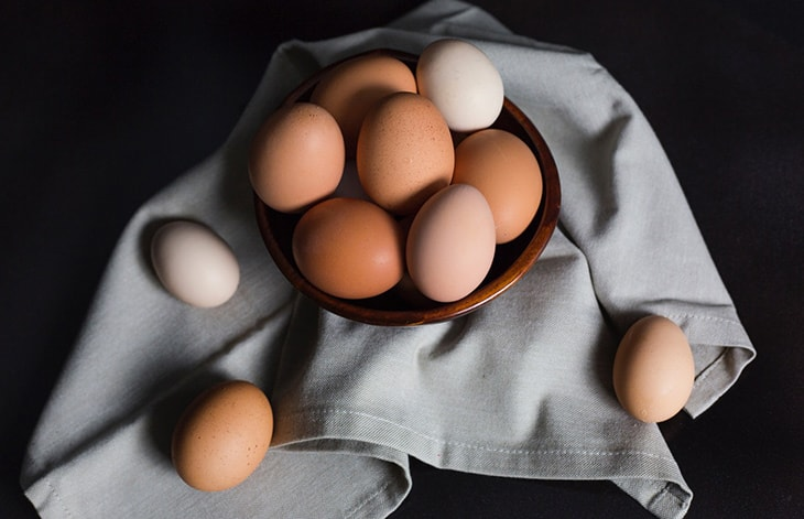 brown, tan, and white eggs in a bowl on top of a gray cloth on a dark background