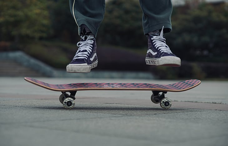 A person's feet in black converse jumping off a red and black skateboard deck