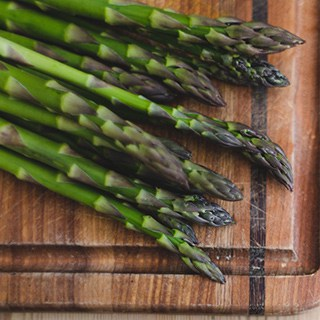 fresh asparagus tops on a cutting board