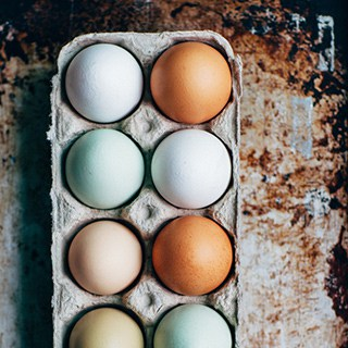 natural white, brown, and green eggs stored in cardboard egg carton