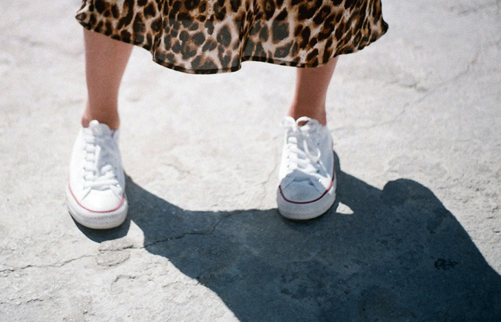 A person's legs and feet wearing a leopard-print skirt and clean, white, canvas sneakers