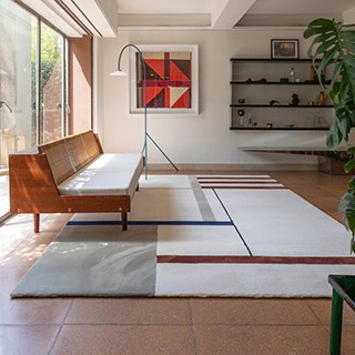 spacious, simple room with geometric rug in the center
