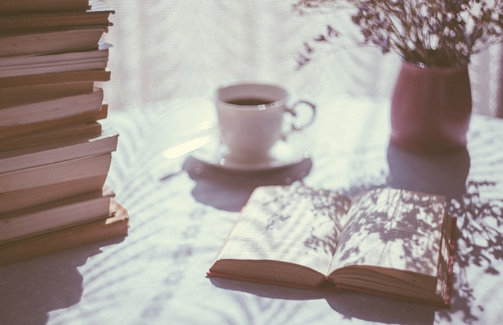 open book, teacup, and vase of flowers on a table beside a stack of books