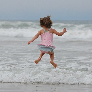 a child wearing a pink and blue ruffled swimsuit jumping on the beach in front of an ocean