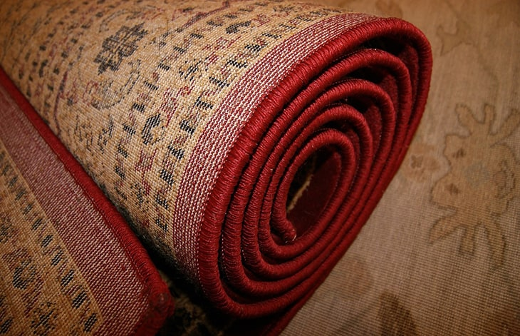 rolled up area rug with red trim