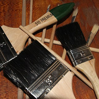 pile of paintbrushes with wooden handles and black bristles