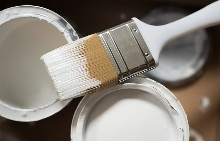 paintbrush dipped with paint lies on open cans of white paint.