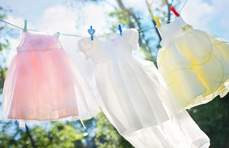 three children's dresses — pink, white, and yellow — hang on a clothesline