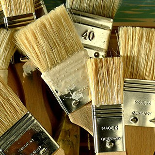 paintbrushes with tan bristles, wooden handles and gold