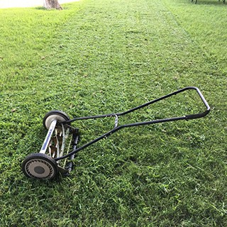Reel lawn mower resting on a gras lawn