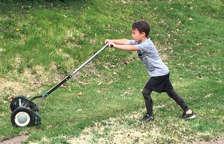 child in gray t-shirt and black pants pushing a reel lawn mower