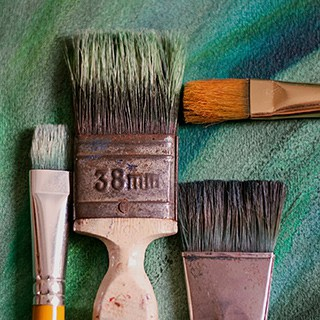 old paintbrushes on green background