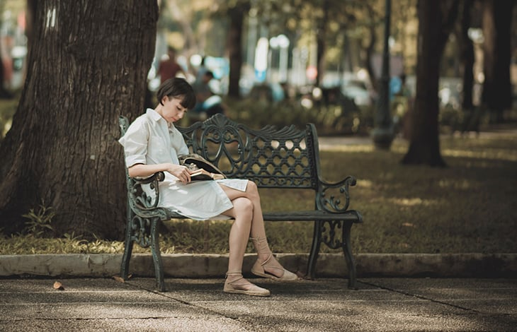 A woman sits on a park bench reading a book