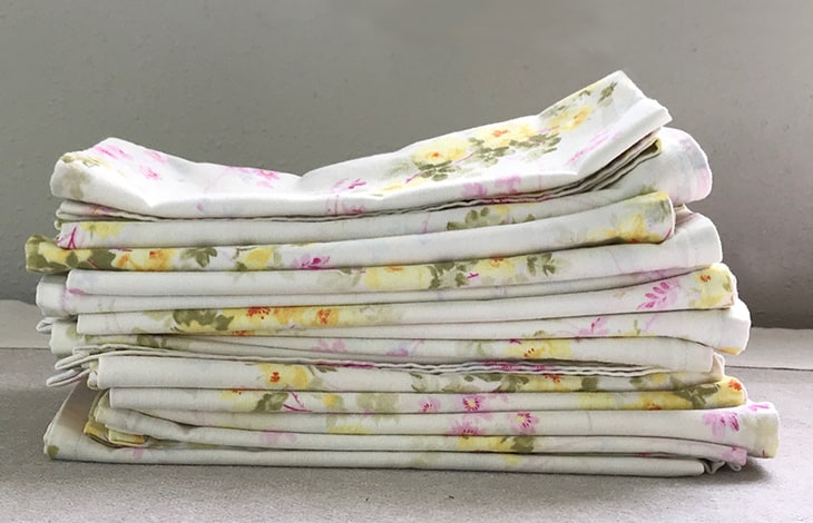 A stack of white, pink, and yellow floral cloth napkins