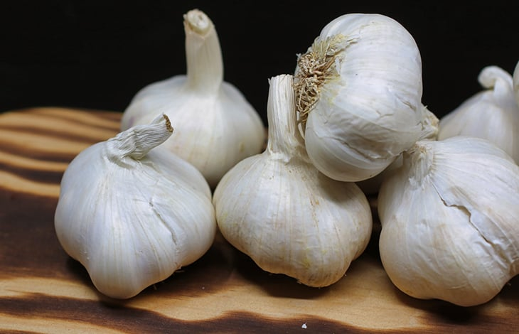 Five garlic bulbs on a wooden cutting board