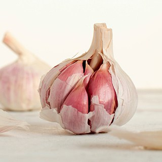 partially peeled garlic bulb with light background