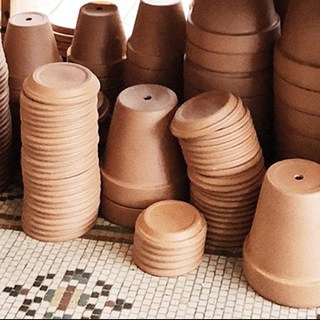 stacked terra cotta pots and saucers on a tiled flour