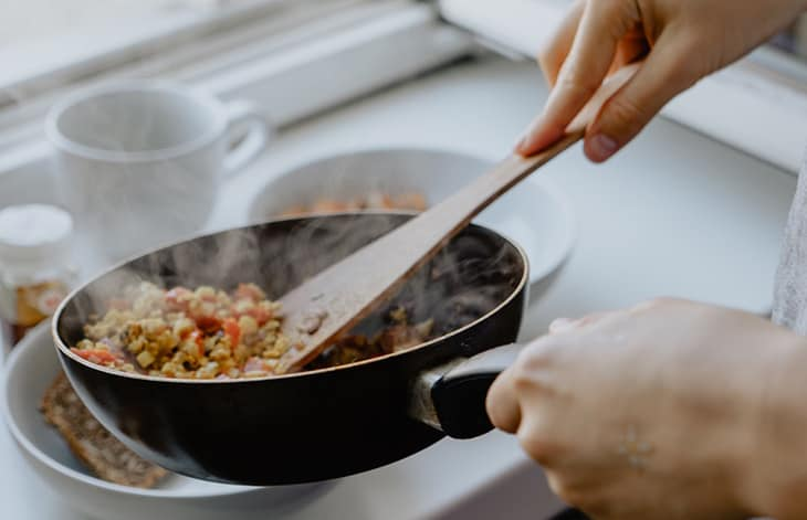 hot leftovers being served from a skillet with a wooden spoon